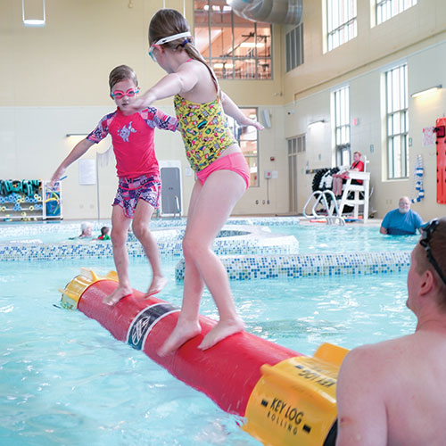 Two girls practice log rolling in the Kroc pool under an instructor's supervision.
