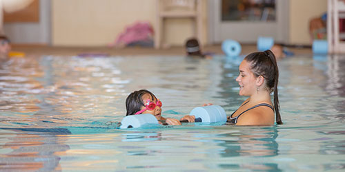 Female swim instructor leads swim lesson with young girl in pink goggles.