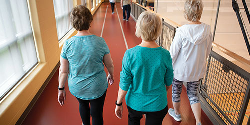Three women walk together on the walking track above the gym.